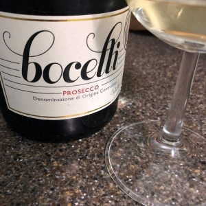 A bottle of Bocelli Prosecco and the base of a wine glass